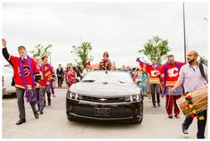 Groom arrives at Barat greeted by his groomsmen in Calgary Flames jerseys. East Indian Wedding photography by Sujata Photography