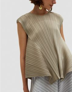 Contemporary top from Pleats Please by Issey Miyake in Beige. Allover tight vertical pleats. Round neckline. Sleeveless. Flared side panels. Straight hem. • Plissé • 100% polyester • Machine wash cold, line dry • Made in Japan NOTE: see sizing ta