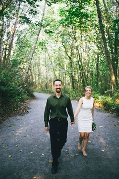 bride and groom hold hands as they walk through forest @myweddingdotcom