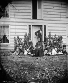 Amund and Siri Rustebakke and Women with Spinning Wheels. Description: Amund Rustebakke, standing in doorway, and Siri Rustebakke, center, sitting, in front of a house with her daughters and daughter-in-law and four spinning wheels. A dog is sitting nearby on the right. 1873 ca.