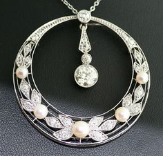 Edwardian diamond pendant. Gorgeous antique circle necklace with hanging European cut 1 carat center diamond. The outer circle beautifully creates a floral design in 18k white gold with natural pearls with more than one carat in diamonds. One of the prettiest antique pendants in our collection, and a very special piece to own.