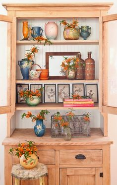 Love the artful arrangement  of this cabinet. Mixing Roseville and dissimilar items. The flowers help to pull it all together. From The Polished Pebble
