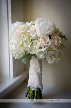 A gorgeous bouquet photographed by Brian Mullins. Classic peonies, roses, hydrangea, and garden roses banded with an accent of fabric from the bride's mother's gown.