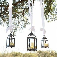 hanging lanterns from trees with candles. great for outdoor wedding decor