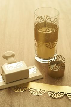 Gorgeous cylinders from Save-on-Crafts.com create simple decor for your table. Punch your paper and place around each cylinder. You can also attach your punched paper to pillar candles with a piece of double stick tape. (Gold paper for cylinders, napkin rings, and votive wraps from http://www.paper-source.com/)