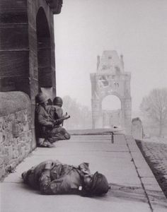 American soldiers take cover on the Nibelungen bridge over the Rhine River, as German snipers on the opposite bank of the Rhine take aim. Worms, Germany. 28 March 1945
