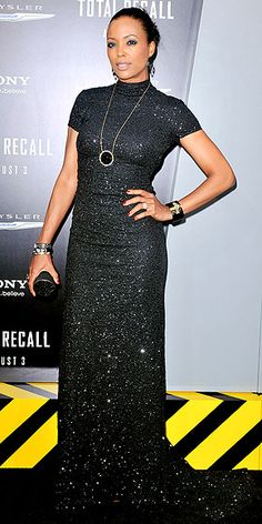 Actress Aisha Tyler accessorizes her dazzling black Pamella Roland gown with dramatic gems by Swarovski, a matching Daniel Swarovski clutch and sleek updo at the Total Recall premiere in Hollywood.