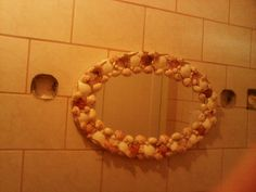 Restaurar un espejo sencillo con caracoles para darle vida.se necesita pintar marco del espejo en crema para después proceder a pegar caracoles con silicona transparente