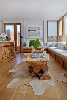 The common area of the guesthouse features a custom-made sectional sofa, two spalted maple cocktail tables, and a hide rug.: