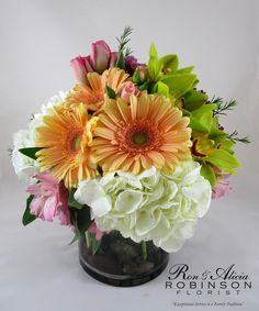 Beautiful Garden-Lovely peach gebera daisies, green cymbidium orchids, pink tulips, pink mini roses, and pink alstromeria combine to form this lovely bouquet. Designed in a clear glass cylinder vase and accented with river rocks this bouquet makes a lovely modern gift. #RAFlorist #RowlandHeightsFlowers #AdministrativeProfessionalsWeek