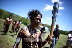 Handout photo issued by Glasgow2014_ A member of the Tjapukai aboriginal dancers carries the Queen's Baton Relay in Kuranda rainforest, Aust...