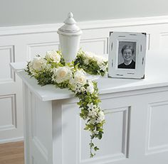White rose flowers, urn, and matching photo frame memorial. Just one of 14 Funeral Urn Memorial Service Table Arrangement Ideas