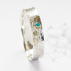 A beautiful, handmade Turquoise Flower Silver Bangle  Add a touch of glamour with our unique gemstone sterling silver bracelet This stunning, unusual chunky turquoise silver bracelet has pretty leaf and flower detailing in brass, upon a gently hammered band of sterling silver. The delicate brass detail makes this bangle look fabulous with both silver and gold tones. Channel the latest nature trends with this stylish semi precious gemstone piece  Available in two sizes small/medium or…