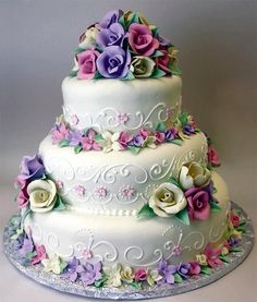 Vibrant three-tier cake with edible flowers. By Konditor Meister Elegant Wedding Cakes. by onlyonemandy