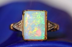 10k gold ring set with a natural Australian opal and two rose cut diamonds. Opal measures 10mm x 7mm. Size: 6. Stone has interior crazing. Very stable. Bright play of color.
