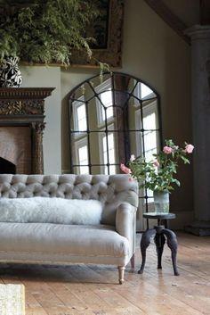 miroir fenetre grand format et sofa capitonné plus petite table tripode