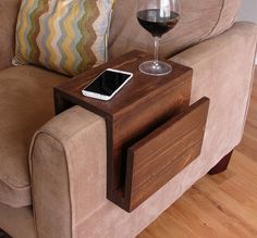 Handmade arm rest tray table with side storage slot for magazines. The perfect addition to a sofa in any home, apartment, condo, or man cave.  It has been sanded down, then stained and sealed with a dark walnut finish.  This piece does not include the accessory items as shown in the pictures.  The color of the stained wood captured in the photos might vary slightly.  Measurement Notes: The width is the arm rest width. The length is the length of the entire assembly along the arm rest (fixed…