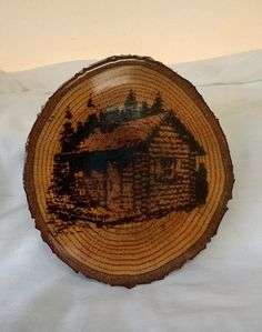 Display of Log Cabin Carving/Engraving on Maple wood slice approx. 1 thick by 5.5 diameter. This item has a thick coat of glossy high build coating.