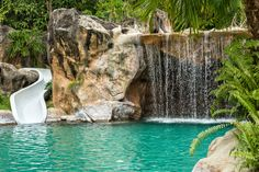 Backyard pool with waterslide, waterfall and large rock wall