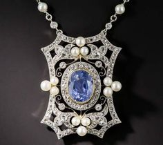 Let's do Edwardian tonight... starting with a pellucid skyblue sapphire, centred in a pendant necklace c.1910, In platinum over 18K yellow gold, there's a halo of rose-cut diamonds in the centre of a foliate, open work octagonal shape frame of rose-cut diamonds and triangular clusters of natural pearls. The chain is newer, and set with pearls and diamonds.