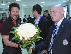 El entrenador argentino del Atlético de Madrid, Diego Simeone (i), recibe un ramo de flores por el día de su cumpleaños a la llegada del club rojiblanco al aeropuerto de Bakú (Azerbaiyán), donde el equipo disputará el martes un encuentro amistoso.