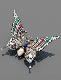 A multigem and gold en tremblant brooch by René LALIQUE, circa 1890. Designed as a butterfly, with spring-mounted wings set with brilliant-cut diamonds, rubies, sapphires and emeralds, the body set with a large oval sapphire and a natural pearl, mounted in yellow gold and silver.