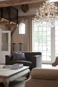 Lovely neutral, slightly rustic living room, with elegant touches like the chandelier and balcony