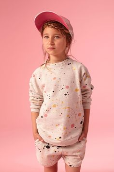 Light grey melange sweater from Soft Gallery. Coloured spatters allover in black, pink, orange and yellow. Round neck, flatlock stitching below neck and at sleeves, round shaped bottom.