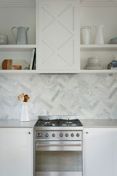 Chic kitchen features white shaker cabinets paired with light gray quartz countertops, Caesarstone Clamshell Quartz, and a marble herringbone backsplash. Red Kitchen, Kitchen Decor, Kitchen Interior, Gray Quartz Countertops, Kitchen Splashback Tiles, Herringbone Backsplash, Herringbone Pattern, Beadboard Backsplash, Hexagon Backsplash