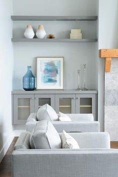 Gray living room alcove boasts gray built in frosted glass cabinets topped with framed blue abstract art, silver candlesticks, and a large recycled blue glass bottle sat below two mounted styled gray shelves accented with cream stacked boxes and a pair of two tone vases illuminated by custom lighting.
