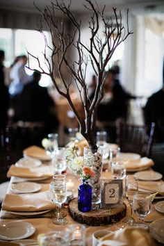 My handmade centerpieces:  Silverwood branch in cylinder vase filled with white/grey marble stones. Cobalt blue vase/bottle with baby's breath, ivory mum, and peach rose. Painted decorative frame with table number. All placed on a tree stump. Stump and table sprinkled with dried baby's breath.