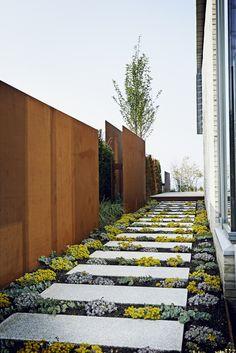 long pavers, plantings, plain wood fence
