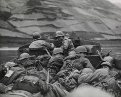 Crouching low in a DUKW for concealment and protection, men of the 89th division, U.S. Third Army, cross the Rhine River at Oberwesel, Germany. March 26, 1945. Photograph by the U.S. Department of Defense