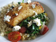 Fish with Sautéed Spinach & Tomatoes  2 TB olive oil, divided  1 onion, thinly sliced  2 cloves garlic, minced  1 c halved or quartered cherry tomatoes  4 c baby spinach  2 fillets of white fish, such as halibut, cod, haddock, or tilapia