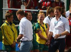 Prince Harry grins as he and Prince William greet members of the Australian and England wo...