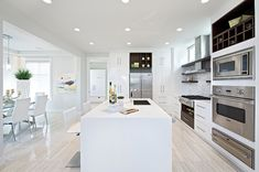 To add individuality and contrast to this all white kitchen space, stainless steel appliances and dark wood upper cabinets are used. Luxury kitchen hardwood flooring provides the final touch to a warm and cozy setting All White Room, All White Kitchen, White Rooms, New Kitchen, Kitchen Ideas, Gloss Kitchen, Kitchen Wood, Kitchen Photos, Kitchen Island