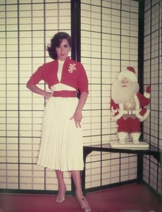Actress Elizabeth Taylor standing next to a Santa Claus doll in front of a shoji screen in 1955.