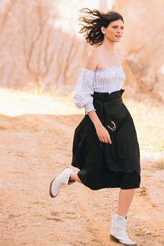 Falda midi de silueta paper bag, con bolsillos laterales, cierre invisible posterior y cinturón adicional.