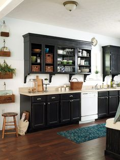 The black paint and crown molding add color and height to the cabinets in this kitchen.