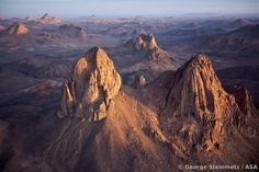 """Aerial view of the volcanic peaks of the Hoggar, just east of Asakrem.  The massif of the twin peaks seen here is known as """"Tezouaï"""" and is ..."""