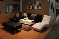 """Sala con sofá esquinero con sección """"chaise"""", un taburete largo y una llamativa """"chaiselounge""""."""