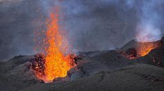 """Lava erupts from the Piton de la Fournaise """"Peak of the Furnace"""" volcano, on the southeastern corner of the Indian Ocean island of Reunion Saturday, Aug. 1, 2015. Spewing red-hot lava, one of the most active volcanoes in the world is currently erupting on this Indian Ocean island, where the world's attention has been focused since a wing fragment believed to be from the missing Malaysian jet was discovered washed up on a beach. (AP Photo/Ben Curtis)"""