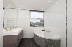 Badkamer met hoekbad, betegeld met mozaïek