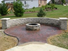 Circle Patio with fire pit and free standing wall with columns and pier caps. PIers at ends of firepit bench could work well as mini table