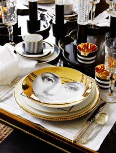Beautiful black and gold table setting with Fornasetti plates by interior designer Megan Winters, via @sarahsarna.