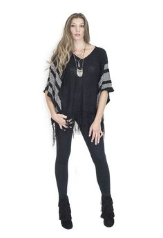 A sweater-knit poncho styled with a white geo graphics is finished with knotted fringe at the hem. Black Poncho, Knitted Poncho, Veronica, Knitting, Skirts, Clothing, Sweaters, How To Wear, Tops