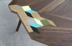 TABLES OF CONTENTS by American designer Paul Isabella is a table designed with complex geometric marquetry and a unique juxtaposition of materials