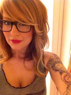 Shoulder length wavy bob, side swept bangs, hipster glasses, red lips, tattoos
