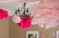 Large paper flowers hung upside down from ceiling for decoration