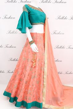 Palkhi fashion exclusive coral lehenga highlighted with elegant teal colored soft pure silk blouse accompanied with cutdana,petite stone and resham work on front and back.Blouse done with trendy bell sleeve look. Party Wear Indian Dresses, Designer Party Wear Dresses, Indian Gowns Dresses, Indian Fashion Dresses, Dress Indian Style, Indian Designer Outfits, Lengha Blouse Designs, Choli Designs, Fancy Blouse Designs